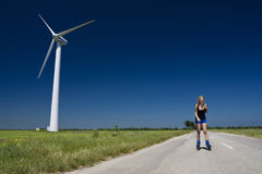 Female at wind power generator. Turbine - alternative and green energy source Royalty Free Stock Photo