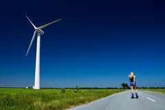 Female at wind power generator. Turbine - alternative and green energy source Royalty Free Stock Photography