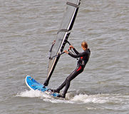Female windsurfer surfboarding Stock Photography