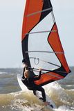 Female windsurfing. At sea. On the top of a wave hanging in the wind stock photography