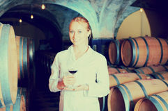 Female wine house worker checking quality of product. Beautiful female wine house worker checking quality of product in cellar Stock Photo