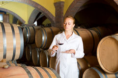 Female wine house worker checking quality of product. Glad female wine house worker checking quality of product in cellar Royalty Free Stock Photo