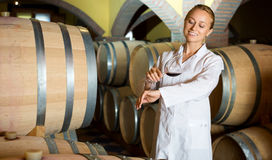 Female wine house worker checking quality of product. Smiling female wine house worker checking quality of product in cellar Stock Images