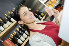 Female wine seller accepting payment from client. Female Stock Images