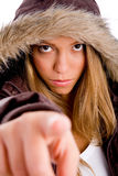 Female with winter coat pointing at camera Royalty Free Stock Images