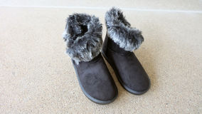 Female Winter Fur Boots or Shoes On The Concrete Floor Background Stock Images