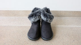 Female Winter Fur Boots or Shoes On The Concrete Floor Background Stock Image