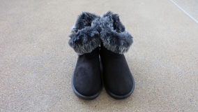 Female Winter Fur Boots or Shoes On The Concrete Floor Background Stock Photos