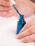 Female wipe brush on glass of nail polish Royalty Free Stock Image