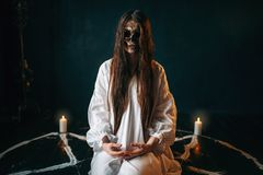 Witch with skull head sitting in pentagram circle. Female witch with skull head sitting in pentagram circle with candles. Dark magic ritual, occult Royalty Free Stock Photography
