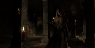 Female wizard. In darkness surrounded by floating candles Royalty Free Stock Photo