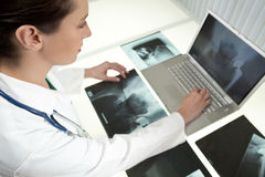 Female Woman Doctor Looking at  X-Rays & Laptop Stock Images