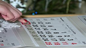 Female woman finger pushing paper calendar marker through last days of year. Time passing. 4K stock footage