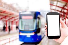 Female / woman / girl with mockup smartphone. Female / woman / girl hand with mockup smartphone / mobile phone with blue tram and public transport station on Royalty Free Stock Photography
