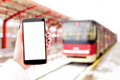Female / woman / girl with mockup smartphone. Female / woman / girl hand with mockup smartphone / mobile phone with blue tram and public transport station on Royalty Free Stock Images