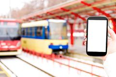 Female / woman / girl with mockup smartphone. Female / woman / girl hand with mockup smartphone / mobile phone with red tram and public transport station on Stock Photography