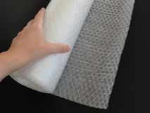 Female or woman hand holds transparent bubble wrap roll for packaging fragile items on black background. Close up royalty free stock photos