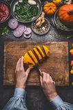 Female woman hands cut pumpkin on cutting board with knife and various vegetables and seasoning ingredients for tasty seasonal dis Royalty Free Stock Photography