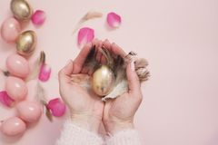 Female, woman hands holding an Easter egg. Pink and Gold Easter Eggs. Pastel Easter Concept with Eggs, Flowers and Feathers Royalty Free Stock Photography