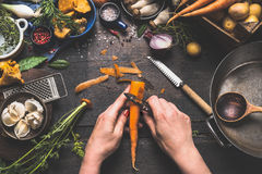 Female woman hands peeling carrots on dark wooden kitchen table with vegetables cooking ingredients. Spoon and tools, top view Royalty Free Stock Photo