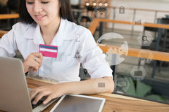 Female woman holding a credit card and using laptop computer for Stock Photography