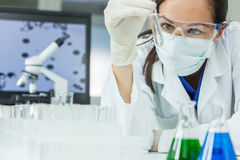 Female Woman Research Scientist With Test Tube In Laboratory. Female medical or research scientist or doctor using looking at a test tube of clear solution in a Stock Photo