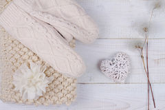 Female woman warm knit Scarf Neckwarmer Circle Cowl and mittens on white wooden rustic background. Shabby chic style. Cozy winter. Royalty Free Stock Image