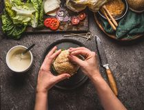 Female women hands holding homemade tasty burger on rustic kitchen table background with ingredients. Top view Royalty Free Stock Images