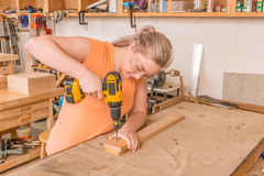 Female woodworker drilling into board Royalty Free Stock Photos