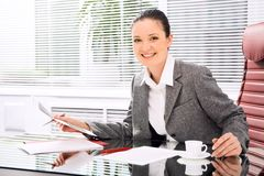 Female at work. Portrait of successful businesswoman holding document while looking at camera with smile in office Stock Photography