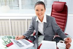 Female at work. Portrait of successful businesswoman holding document while looking at camera with smile in office Stock Image