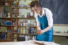 Female Worker in Apron Moulding a Piece of Clay in Professional Workshop. Pottering and Clay Making Concepts. Female Worker in Apron Moulding a Piece of Clay in Royalty Free Stock Photo