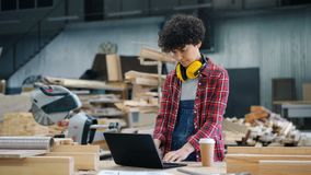 Female worker using laptop in wood workshop typing standing in workplace alone. Female worker attractive young girl is using laptop in wood workshop typing stock footage
