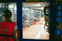 Female worker on beer factory. portrait woman in robe, standing on background line Food production, Inspection management control royalty free stock photos