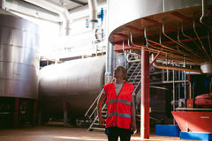 Female worker on beer factory. portrait woman in robe, standing on background line Food production, Inspection management control royalty free stock images