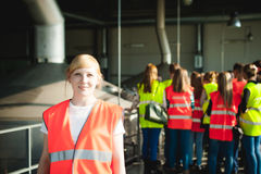 Female worker on beer factory. portrait woman in robe, standing on background line Food production, Inspection management control. Blonde woman in overalls, on stock images