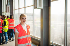 Female worker on beer factory. portrait woman in robe, standing on background line Food production, Inspection management control. Blonde woman in overalls, on stock photography