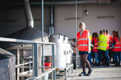 Female worker on beer factory. portrait woman in robe, standing on background line Food production, Inspection management control. Blonde woman in overalls, on stock image