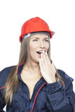 Female worker in blue overall and red safety helmet. Yelling Stock Images