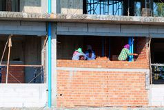 Female worker bricklayer laying brick a wall construction in industrial building site stock image