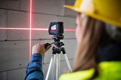 Young woman worker with laser on the building site. Female worker on the building site. Beautiful young woman with line laser level. House construction Royalty Free Stock Photography