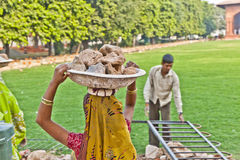 Female worker carries rock waste on her hat Stock Photos