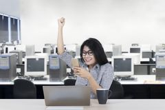 Female worker celebrating her success. By lifting hand while reading good news on the smartphone. Shot in the office Royalty Free Stock Photos