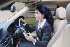 Female worker with cellphone driving car Royalty Free Stock Photos