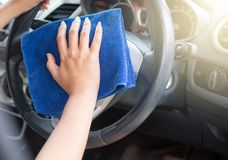 Female worker cleaning car inside dashboard. Cropped image Royalty Free Stock Image