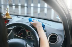 Female worker cleaning car inside dashboard. Cropped image Royalty Free Stock Photos