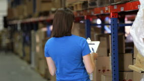 Female Worker With Clipboard In Warehouse stock video