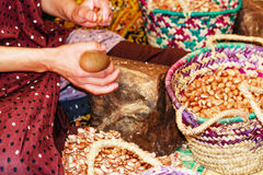 Female worker cracking Argan nuts Royalty Free Stock Images
