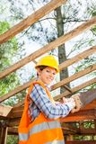 Female Worker Cutting Wood With Handsaw At Site Stock Photos