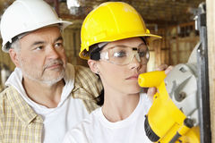 Female worker cutting wood with a power saw while male worker standing behind Stock Photos